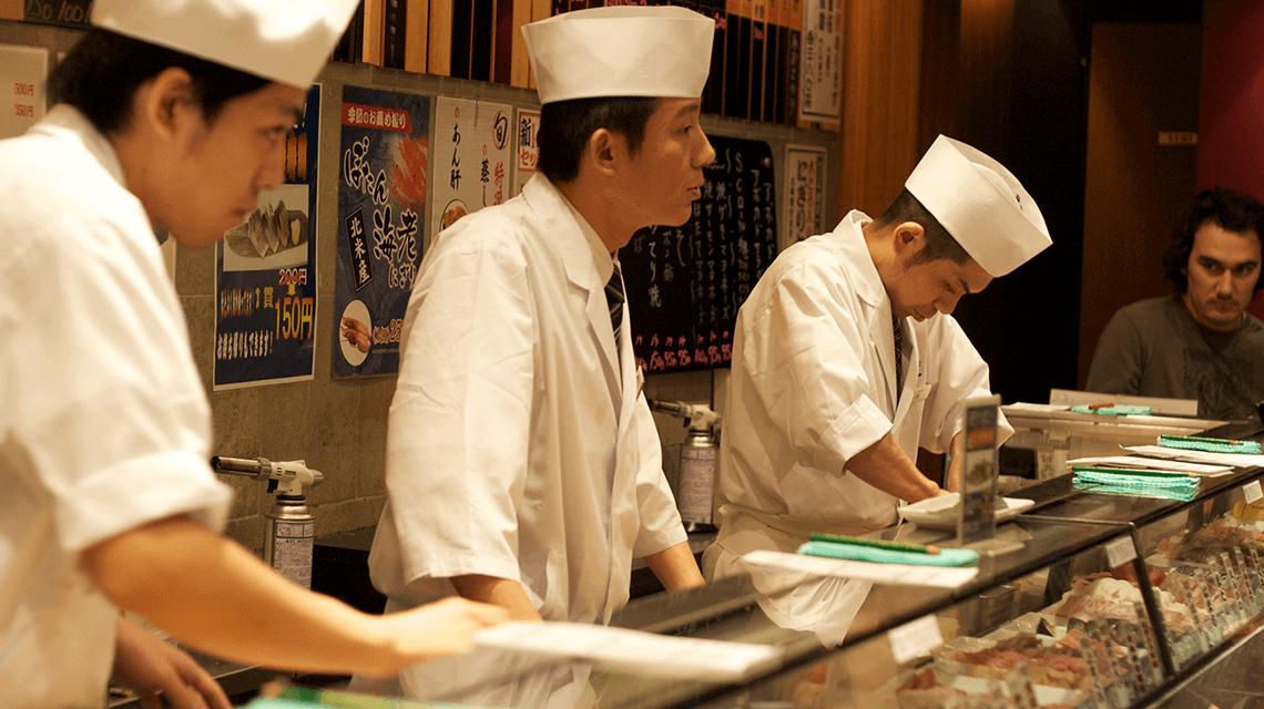 Chefs serving customers at a sushi bar in Shibuya, Tokyo, Japan