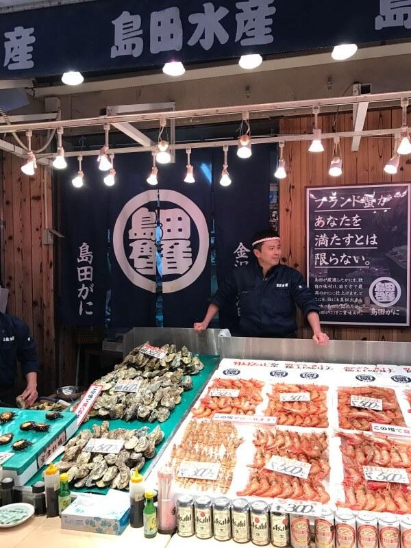 Seafood seller and stall at Omicho Market in Kanazawa, Japan.