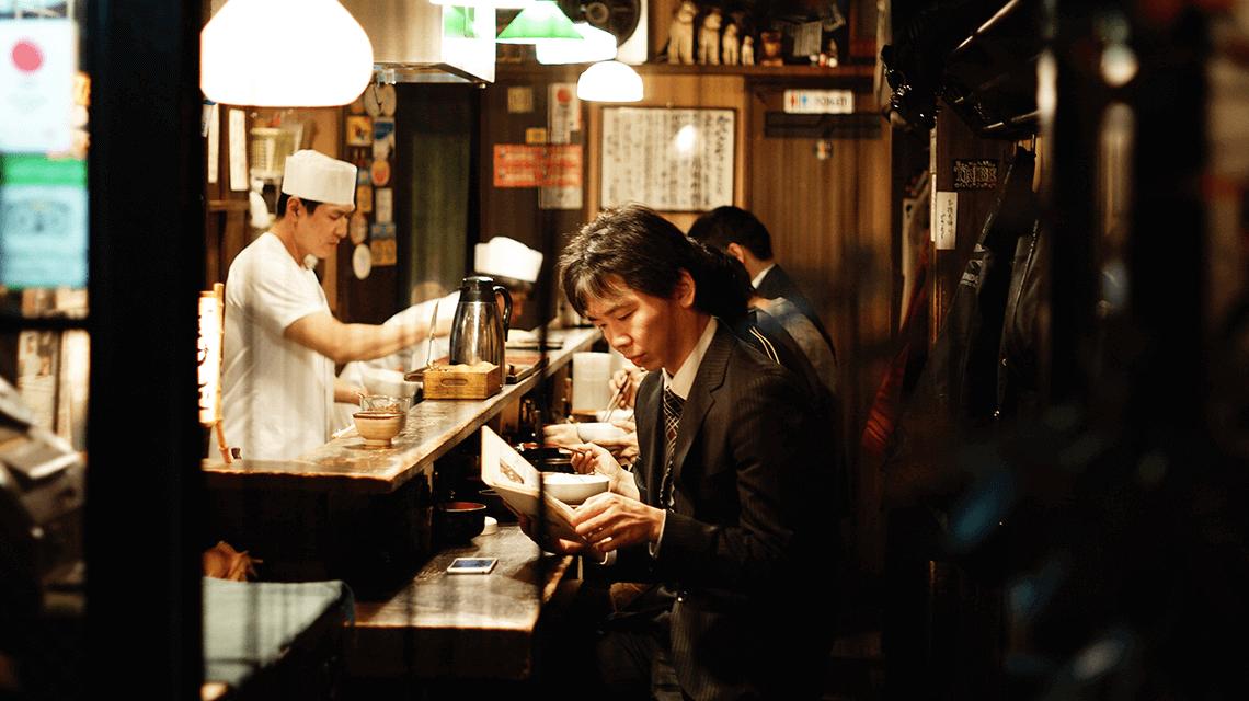 A Japanese man browses the menu in a small izakaya in Shinjuku, Tokyo, Japan