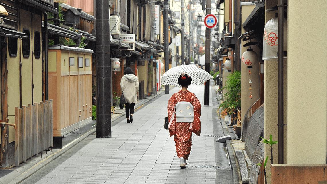 Japanese woman wearing a kimono walks down a street in Kyoto, Japan