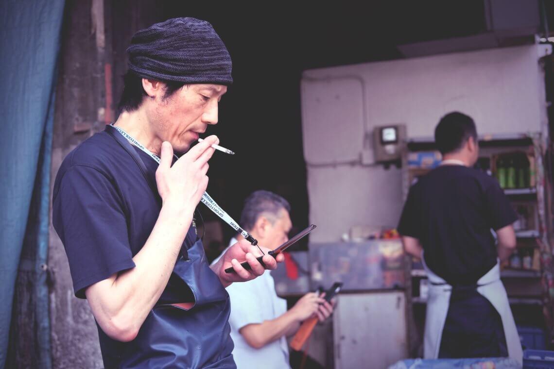 Tsukiji worker taking a cigarette break, at Tsukiji Market in Tokyo, Japan